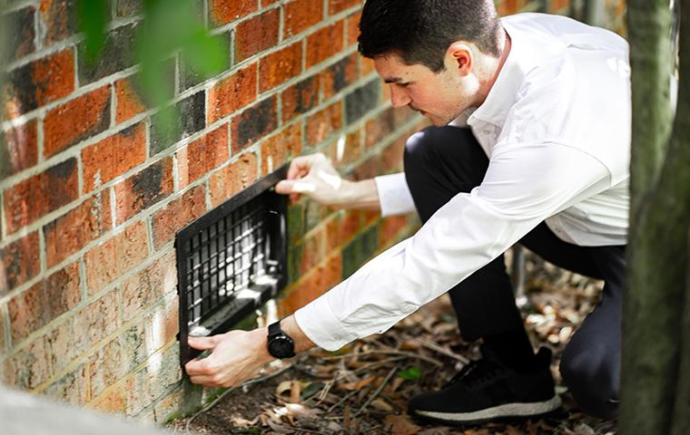 a pest control service technician installing a termite bait station near the exterior of a home in charlotte north carolina for termites