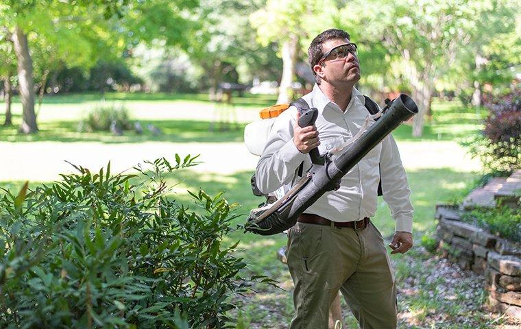 a pest control service technician arriving to perform mosquito reduction treatments on the exterior of a home in charlotte north carolina