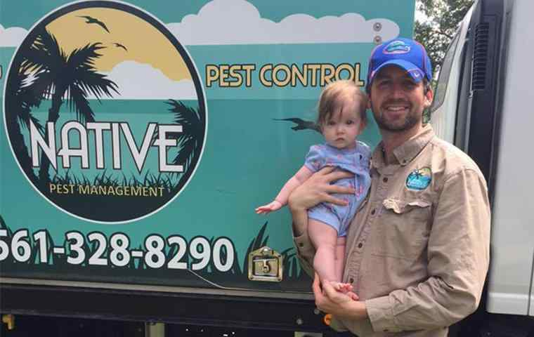 native pest management tech standing in front of company truck
