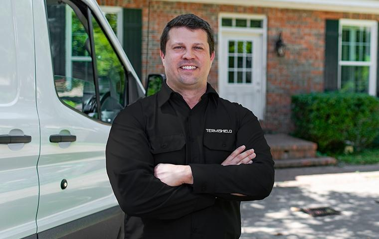 a pest control service technician posing outside of a home in hammond indiana