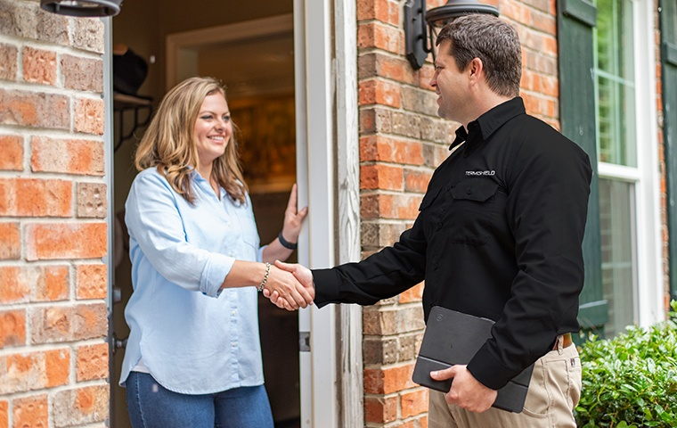 a pest control service technician greeting a residential homeowner in niles michigan