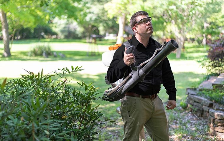 a pest control service technician preparing to perform pest treatments outside of a home in dowagiac michigan