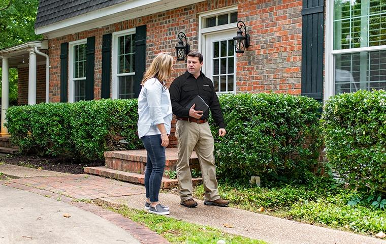 a pest control service technician discussing home pest control services with a homeowner in elkhart indiana