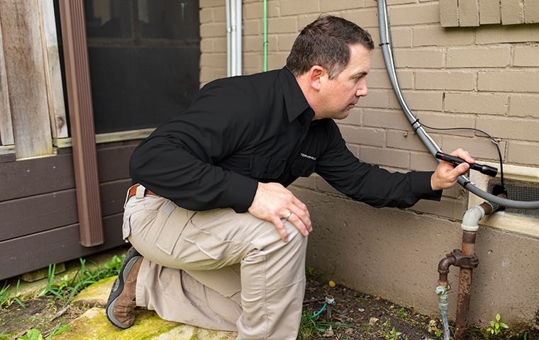 a pest control service technician inspecting the exterior of a home in edwardsburg michigan