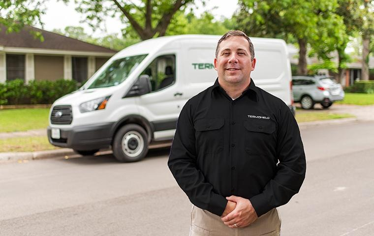 a pest control service technician posing in front of a company vehicle outside of a home in mishawaka indiana