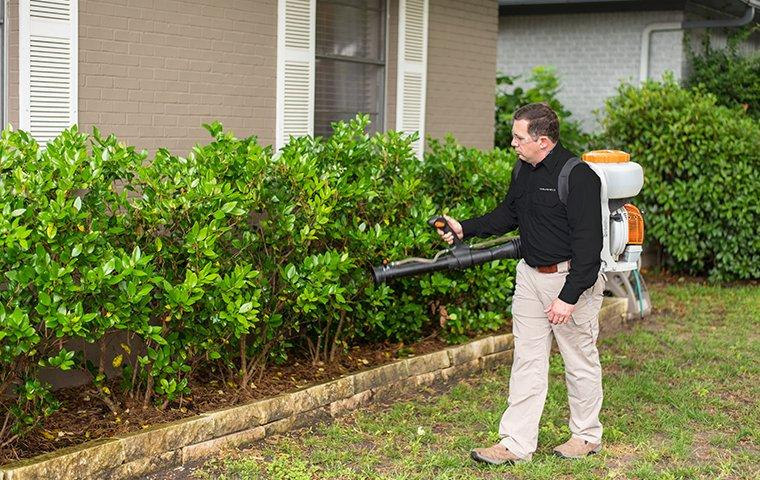 a pest control service technician performing mosquito misting services on the exterior of a home
