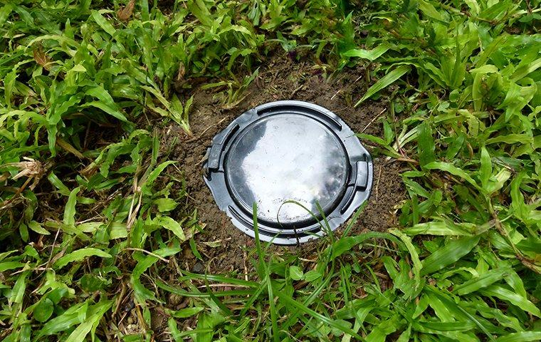 a termite bait station installed in the ground outside of a home in south bend indiana