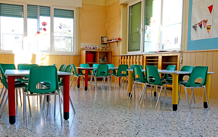 interior of a daycare room without children filled with small tables and chairs