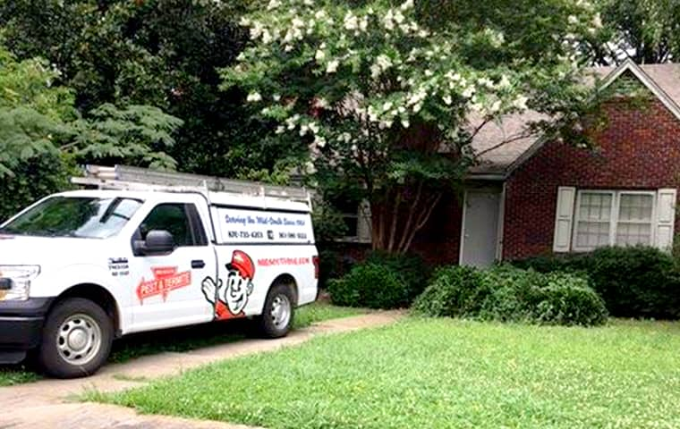 a mid south pest and termite company vehicle parked outside of a home in memphis tennessee