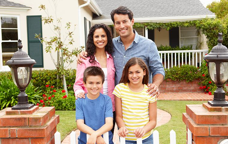 a happy family of four in front of their home in plano texas