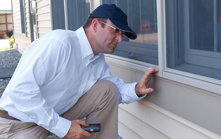 a technician performing an exterior inspection at a home in richardson