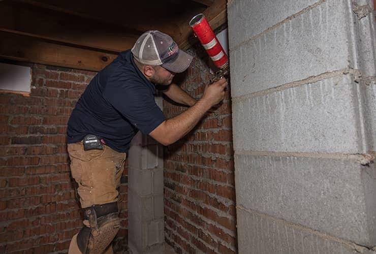 technician performing moisture control in a basement
