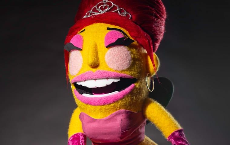 a hand puppet of a fancy dressed up queen bee with a red bee hive hair style and shines pink tiara