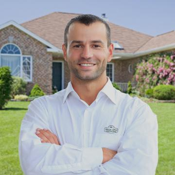 a smiling technician standing in front of a home in marshall