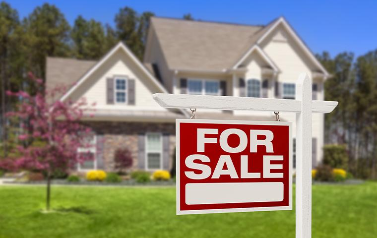 house with for sale sign in front