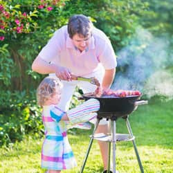 father helping daughter barbecue