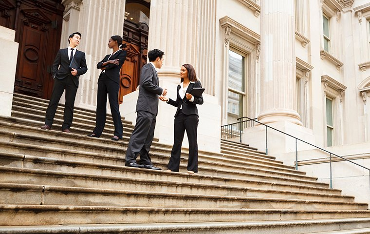 men and women on the steps of a government building