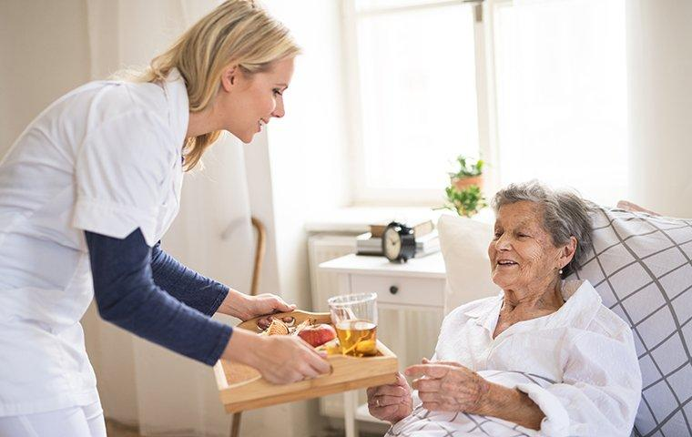 a healthcare worker assisting an elderly patient in a retirement facility