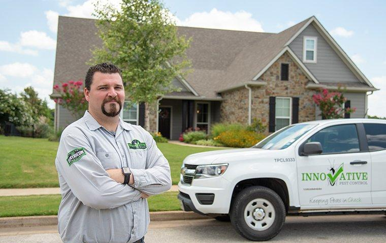 a pest control tech in front of house