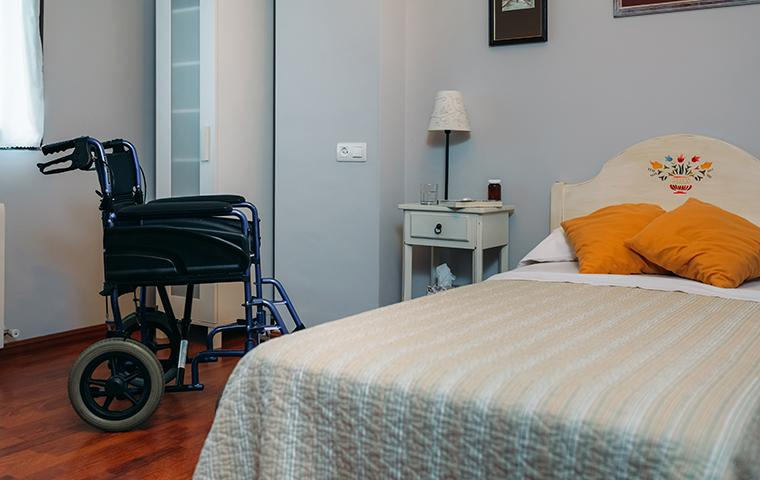 empty wheel chair next to bed in retirement home