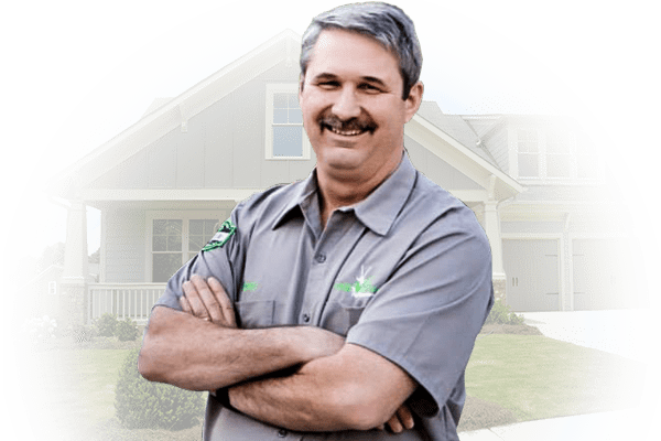 innovative pest control owner standing in front of home