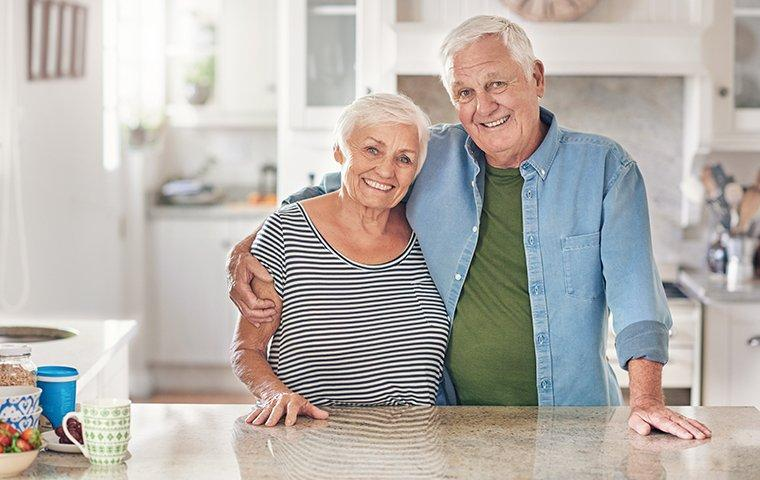 elderly couple standing in their kitchen