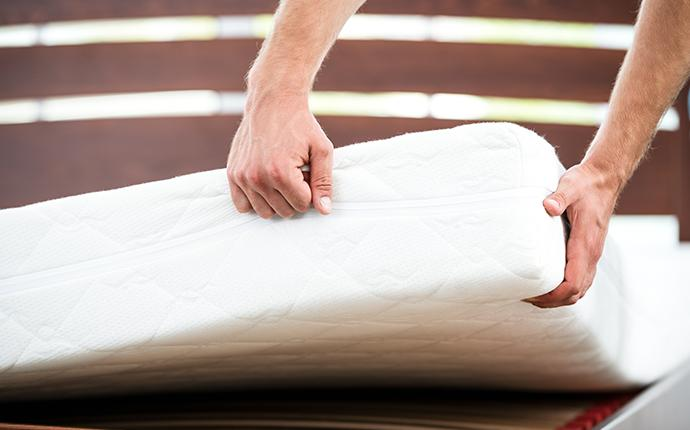 a person pulling up the corner of an impeccably clean mattress