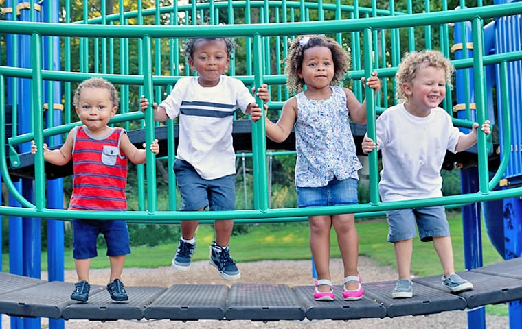 four young children standing on playground equipment at a baton rouge louisiana daycare