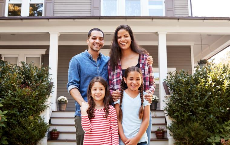 a family standing in front of a baton rouge louisiana suburban home