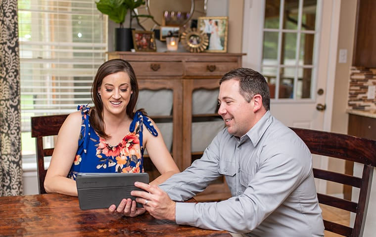 a pest control technician and homeowner looking at at tablet at a table in baton rouge louisiana