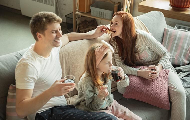 couple eating pizza on couch with daughter