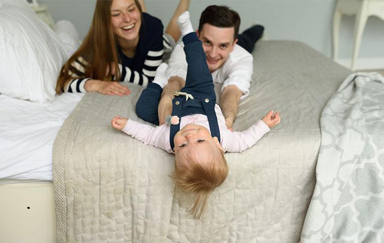 family laying on a bed