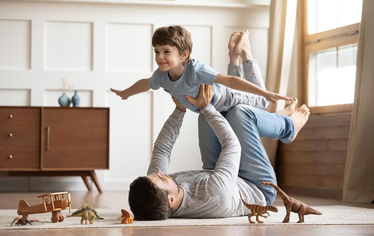 a father and son playing in living room