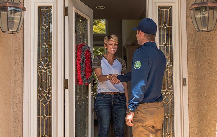 a pest control technician greeting a customer