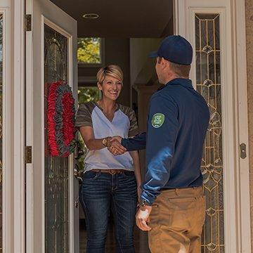 a pest technician greeting a customer