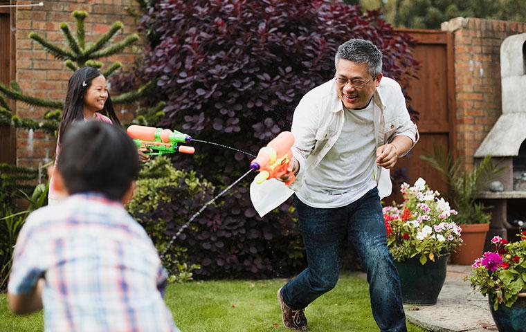 father and kids shooting squirt guns
