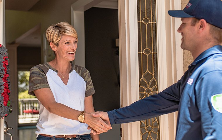 a pest control expert shaking hands with a customer