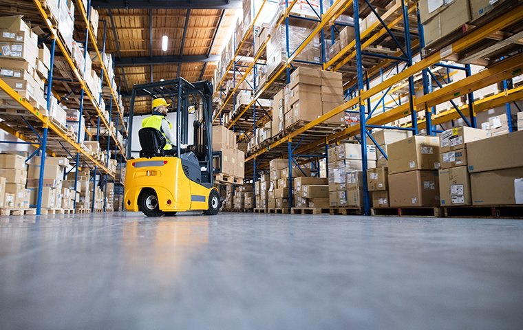 a worker driving a forklift in a warehouse