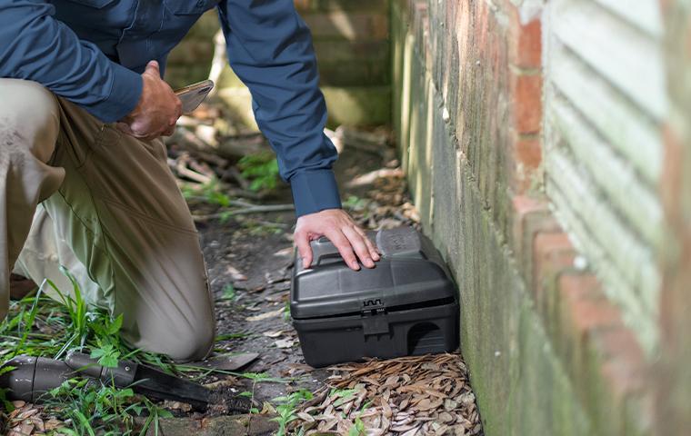 technician kneeling over rodent bait box