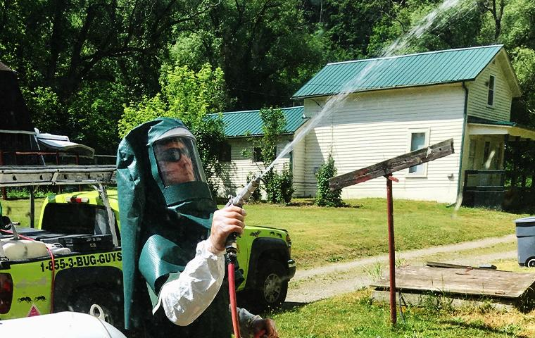 technician spraying outside a home