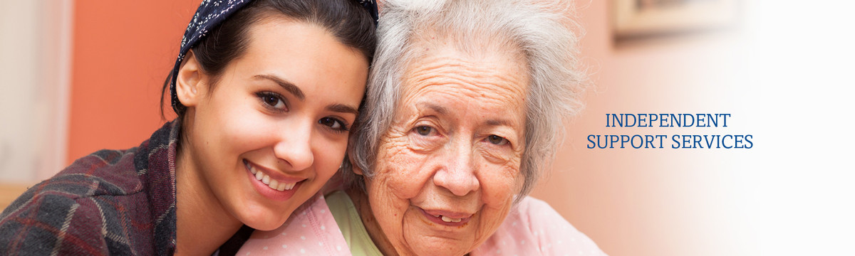 A young woman and an older woman sit close and smile. Our suport services help elderly and disabled individuals with housekeeping, errands and other daily tasks.