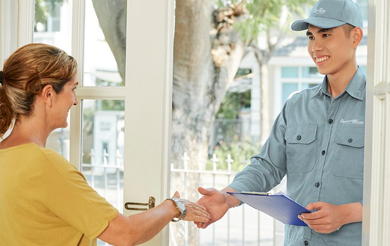 a pestmaster services tech shaking hands with a client