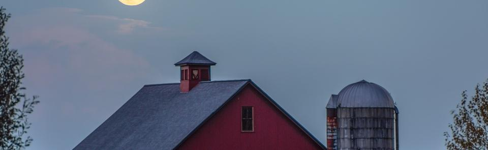 A red barn at night under the moon to the left of a silver silo.