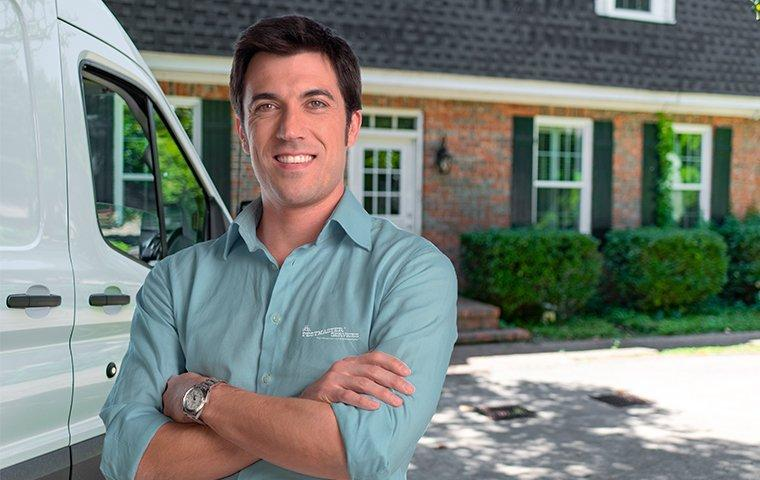 a pest expert in front of a house