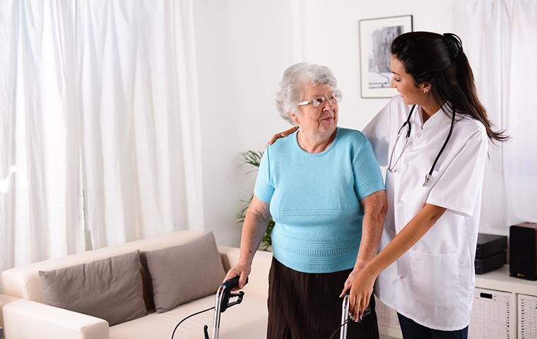 friendly nurse helping elderly woman with walker
