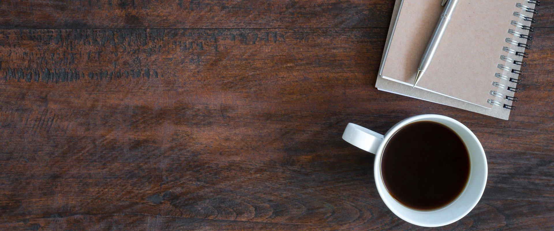 a journal and a cup of coffee on a table