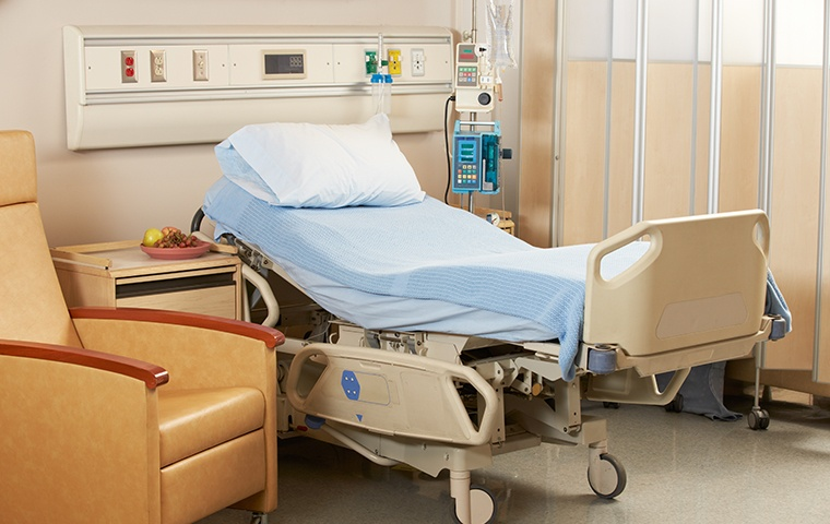 empty hospital bed in hospital room