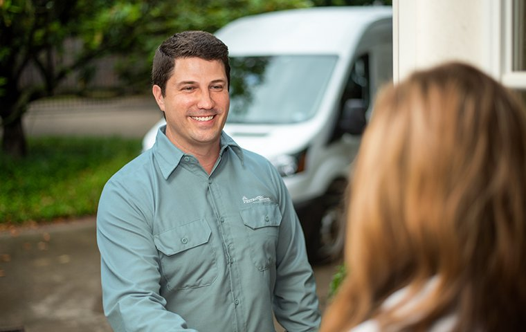 a friendly pest tech greeting a homeowner