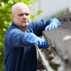 man keeping his gutters clear