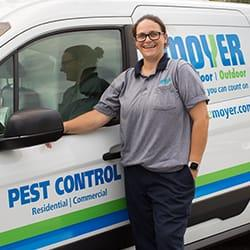 a professional pest control technitian smiling as she is staring next to a moyer pest control service truck offering general pest control services in the souderton pennsylvania area